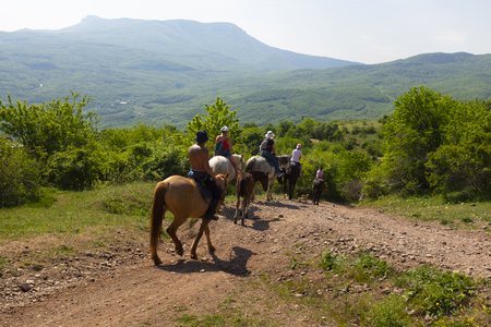 Group of tourists on the mountain equestrian trip on horses around the Ghost valley near Alushta, Crimea.