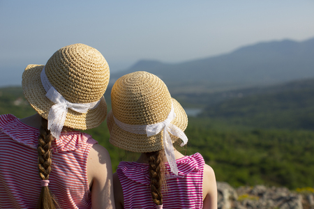 Back view of two little cute girls in lovely summer straw caps with lace ribbons are standing together and looking at the beautiful landscape in mountains near Ghost valley and the Black sea, Crimea.