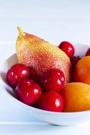 Fruit in a bowl. Red cherry, apricots and Forelle pear in a white bowl on light blue background.