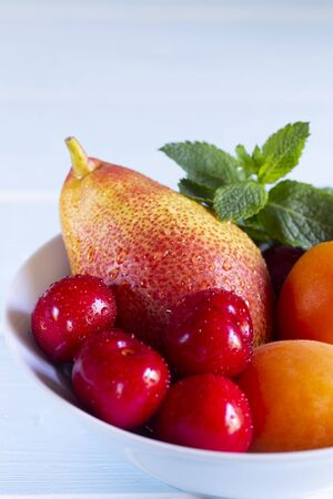 Fruit in a bowl. Red cherry, apricots, Forelle pear with fresh mint in a white bowl.