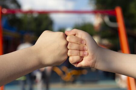 Kids are doing fist bump on the playground.