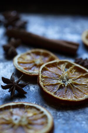 Dry orange, cinnamon stick and anise on old  grey and black baking tray. Rustic, closeup.