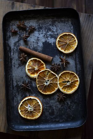 Dry orange, cinnamon stick and anise on old  grey and black baking tray. Rustic, top view, flat lay.