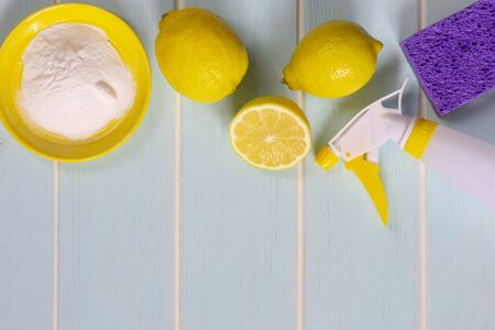 Natural products for eco cleaning. Lemon, baking soda and vinegar for eco housekeeping. Yellow and violet objects. Blue wooden background.