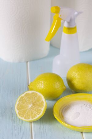 Natural products for eco cleaning. Lemon, baking soda, vinegar and paper towels for eco housekeeping. All objects, lemon, bowl, pump sprayer  are in yellow color. Blue wooden background. Stock Photo
