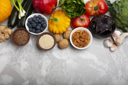 Mix of fresh healthy vegetarian ingredients of vegetables, nuts, seeds, bran, fruit and berries on a gray cement background. Top view, copy space. Stock Photo