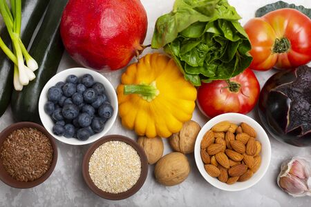 Mix of fresh healthy vegetarian ingredients of vegetables, nuts, seeds, bran, fruit and berries on a gray cement background. Top view.