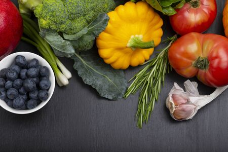 Mix of fresh healthy vegetarian ingredients of vegetables, fruit and berries on a black wooden background. Top view. copy space. Stock Photo
