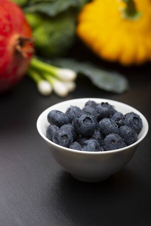 Blueberry with  drops of water in a bowl with a background of vegetables, fruit and on a black wooden table.