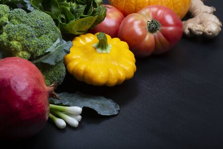 Mix of fresh healthy vegetarian ingredients of vegetables, fruit, herb and root on a black wooden background. Top view, copy space.