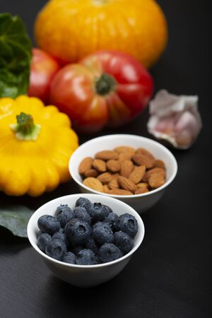 Blueberry with  drops of water in a bowl with a background of vegetables, fruit and nuts on a black wooden surface.