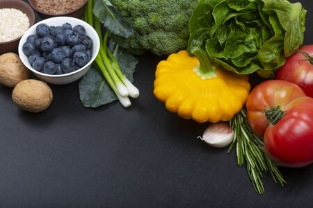 Mix of fresh healthy vegetarian ingredients of vegetables, berries, nuts and cereals on a black wooden background. Copy space.