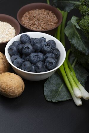 Mix of healthy vegetarian ingredients of vegetables, seeds, bran and berries on a black wooden background. Top view. Stock Photo