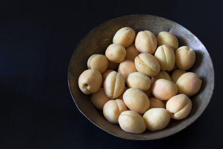 Fresh ripe apricots in a vintage brass basin on black background.