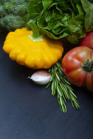 Mix of fresh healthy vegetarian ingredients of vegetables and herb  on a black wooden background. Copy space. Stock Photo