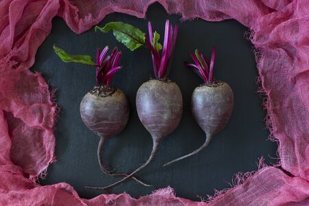 Tree little fresh homegrown organic young beets with green leaves surrounded by purple fabric on dark wooden background.