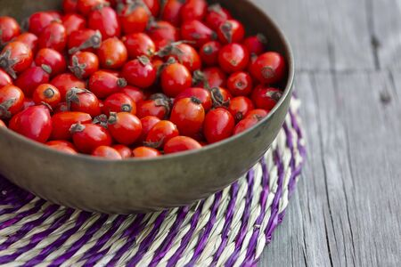 Rosehips in vintage brass bowl on straw tray.