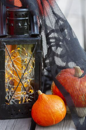 Pumpkins and Halloween style vintage lamp with black cover, orange candle and yellow lights on wooden surface. Banco de Imagens