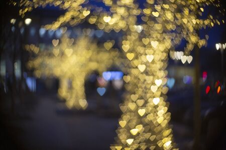 Blurred Chrismas and New Year illumination on the street. Trees with bokeh heart shape lights. Abstract New Year background.