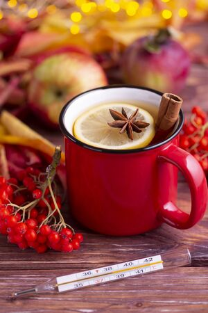 Red cup of tea with lemon, anise and cinnamon on the wooden table with glass medical thermometer showing high temperature, rowan, apples. Natural treatment for colds and flu.