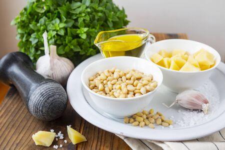 Pesto sauce ingredients on wooden table. Archivio Fotografico