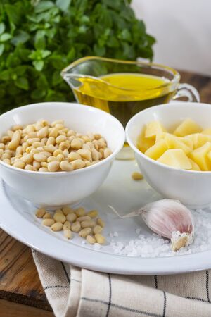 Pesto sauce ingredients on wooden table.