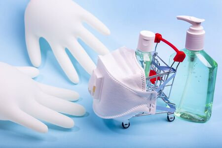 Bottle of alcohol hand gel sanitizer in a grocery supermarket trolley cart  and pair of latex medical hand gloves for coronavirus prevention.