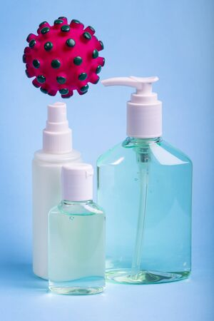 Bottles of alcohol hand gel and spray liquid sanitizer for coronavirus prevention. COVID-19 concept with coronavirus model on blue background.