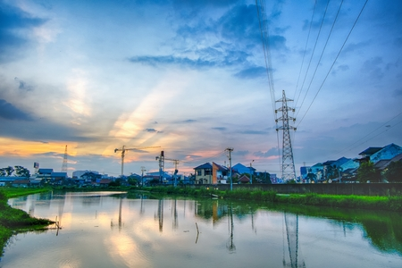light transmission: Sunset in urban areas, featuring transmission towers, ponds that make beautiful reflection, crane, rays of light and many houses Stock Photo