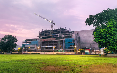 High building construction progress, captured from far away at dawn. Featuring tall crane, with safety lamp still light up