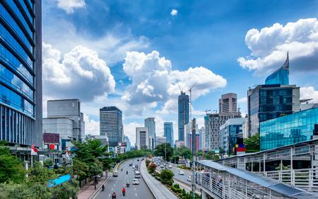 ジャカルタ、インドネシアの美しいスカイライン。近代的な超高層ビルと美しい青い空と白い雲が日光で中等度のトラフィックの大きな道路を示し 報道画像