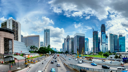 Panorama of beautiful skyline of Jakarta, Indonesia. Showing modern skyscraper buildings and beautiful blue sky and white cloud at daylight and big road with moderate traffic. Captured in Jend. Sudirman Street.