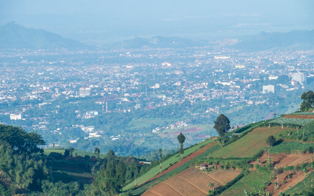 Aerial view of plantation on top of the hill and scenery of bandung city from faraway, captured  from Moko Hills when weather is sunny, Bandung, Indonesia Stock Photo