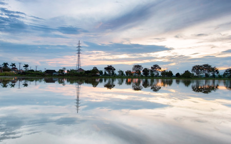 Transmission tower, electricity pylon or a power pylon, standing majestically in front of large lake or pond, also with beautiful cloud at sunrise. Stock Photo