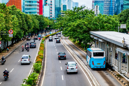 Public transport bus stopped in bus stop, waiting until passenger get in, in busy street at Jakarta, Indonesia. Editorial