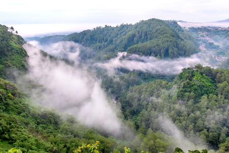 Misty hill,  mist flowing between two hill in the top of the forest. Located in Keraton Cliff, Bandung, West Java, Indonesia Stock Photo