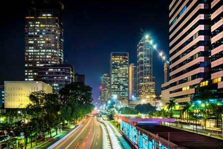 M.H タムリン通り、ジャカルタ ジャカルタ幹線道路における車両交通の光跡。また、道路の側で美しい skyscrapper の行を示しています。都市の地平線