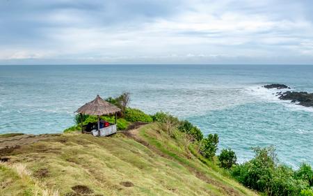 展望台や美しい海と曇りの日で、海の中のサンゴ礁が直面している、海岸の近くの丘の上の小屋。Menganti ビーチ、Kebumen、インドネシアでキャプチャ