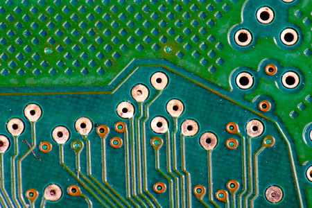 close up photo of green printed circuit board or PCB, showing many lines of  connector made of copper