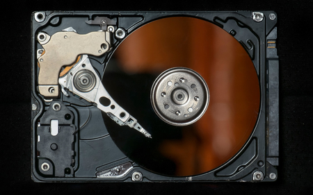 binary file: Beautiful photo of inside of harddisk, as symbol of computer storage, isolated in black background. Showing harddisks  platter and harddisk head on the top of the platter, captured from the side.