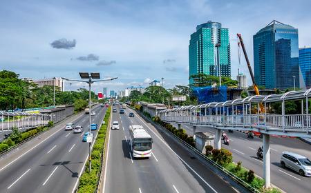 ジャカルタ、インドネシアで捕獲白バスと大きな有料道路や高速道路、またショー歩道橋、skyscrapper 側に建物の多くの他の車を渡します。 報道画像