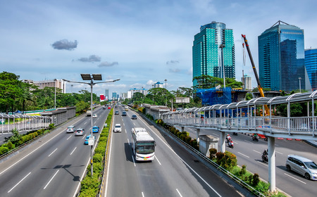 Passing white bus and many other vehicle  in big toll road or highway, also show pedestrian bridge and skyscrapper building on the side, captured in Jakarta, Indonesia. Editorial