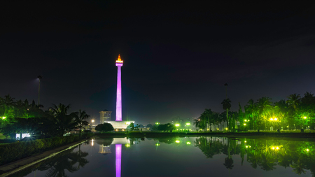 National Monument (Monas) at night, in front of big pool, create beautiful reflection of this monument., this is one of iconic monument in Jakarta, Indonesia Editorial