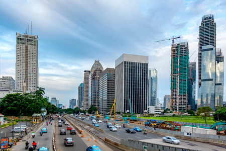 Beautiful skyline of Jakarta, Indonesia. Showing modern skyscraper buildings and beautiful  sky and white cloud at afternoon and big road with moderate traffic. Captured in Jend. Sudirman Street. Editorial