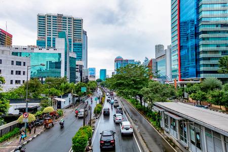 ジャカルタとそのトラフィックの道の道路の両側に超高層ビルの写真。ラスナと述べた通り、インドネシアで捕獲。