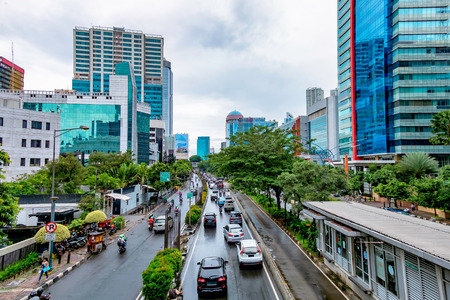 Photo of big road in Jakarta and its traffic, with skyscraper buildings in the both side of the road. Captured in Rasuna Said Street, Indonesia.