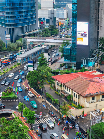 Photo  of intersection in Jakartas main road, in near Sudirman street area. Contain busy traffic, cars and motorcycle also  building with red colored roof and big skyscrapper.  Urban Skyline, Building Exterior, Capital Cities