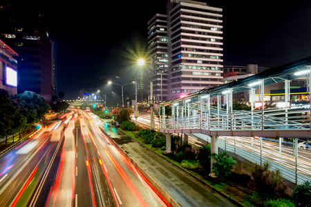 Light trail of vehicle traffic in Jakarta main road, M.H Thamrin Street,  Jakarta. Also showing row of beautiful skyscrapper in the side of the road. Urban Skyline, Building Exterior, Capital Cities, Night photography Editorial