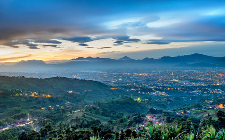 Hills and beautiful city light at night, seen faraway from top of the hilll, also showing shadow of mountain in the background, captured in Bandung, Indonesia Stock Photo