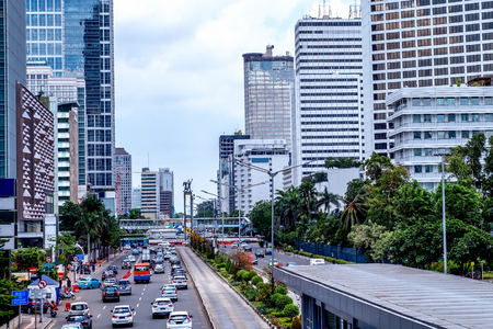 Busy traffic near Bundaran Hotel Indonesia, or Hotel Indonesia roundabout. Featuring skyscraper and Selamat Datang Monument.  Urban Skyline, Building Exterior, Capital Cities